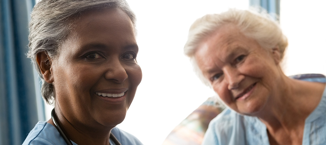 a health coach on the left smiling at the camera with her patient smiling at the camera on the left